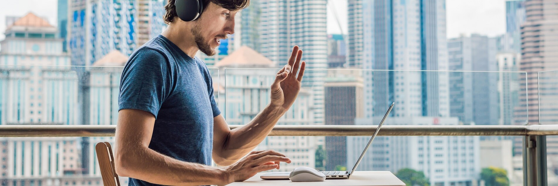 Mann mit Kopfhörern sitz am Laptop